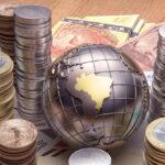 globo terrestre com o brasil em destaque em meio a moedas e notas de Real